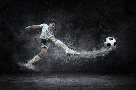 Splash of drops around football player under water Foto de archivo