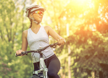 individual sport: Portrait of beautiful woman on the bicycle in the park. Stock Photo