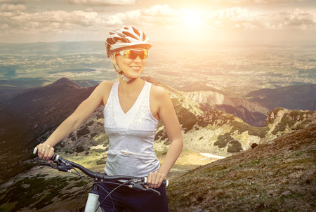 personas saludables: Mujer hermosa en casco y gafas de permanecer en la bicicleta por las montañas.
