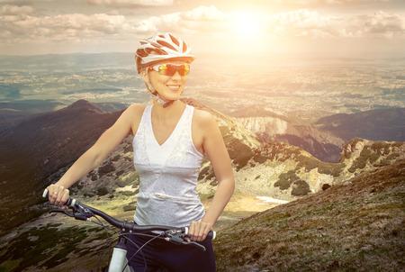 bewegung menschen: Schöne Frau in Helm und Brille zu bleiben auf dem Fahrrad in der Umgebung von Bergen.
