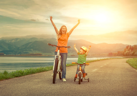 woman bike: Happiness Mother and son on the bicycles funning outdoor Stock Photo