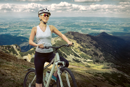 women sport: Beautiful woman in helmet and glasses stay on the bicycle around mountains.