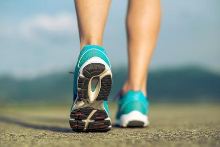 deportistas: Pies Runner atleta que se ejecutan en el camino bajo la luz del sol.