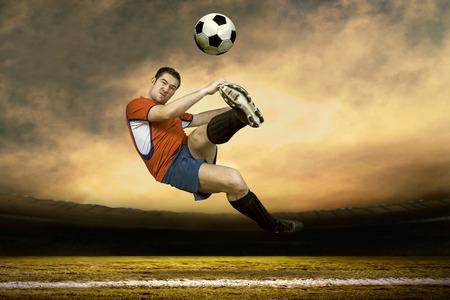 sotto la pioggia: Giocatore di calcio con palla in azione sotto la pioggia all'aperto Archivio Fotografico