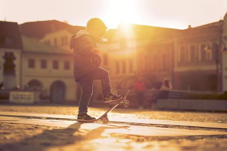 skateboard: Child with skateboard on the street at sunset light. Stock Photo