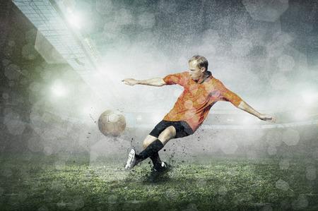 sotto la pioggia: Calciatore con la sfera in azione a stadio sotto la pioggia.