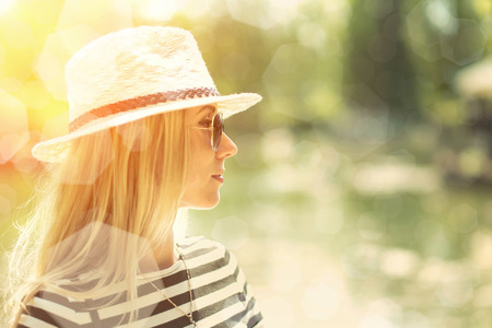 one woman: Portrait of blond woman in white hat and sunglasses on the lake background. Stock Photo