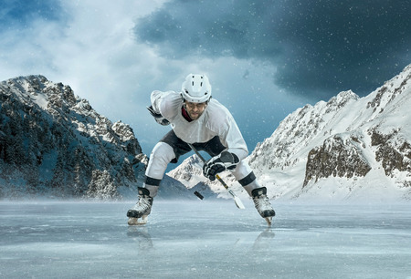 hockey skates: Ice hockey player in action outdoor around mountains