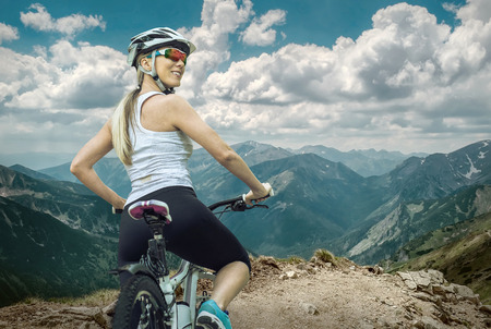 glasses: Beautiful woman in helmet and glasses stay on the bicycle around mountains.