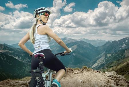 Mooie vrouw in de helm en bril te blijven op de fiets rond bergen.