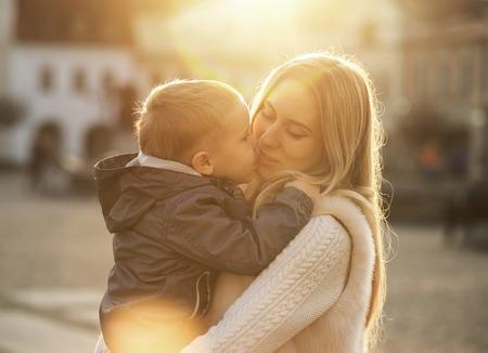 hombros: Madre Felicidad e hijo en la calle en día soleado.
