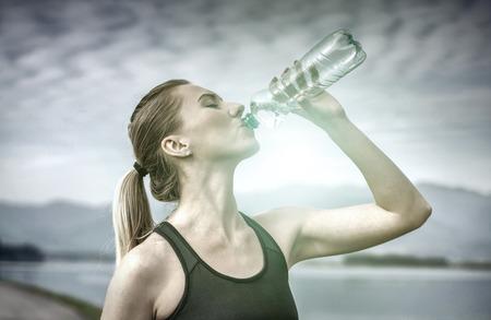 agua potable: Hermosa mujer después de correr, beber agua bajo el cielo