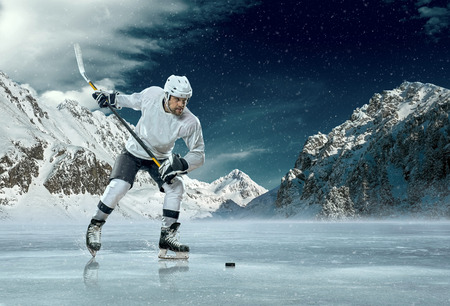 hockey goal: Ice hockey player in action outdoor around mountains