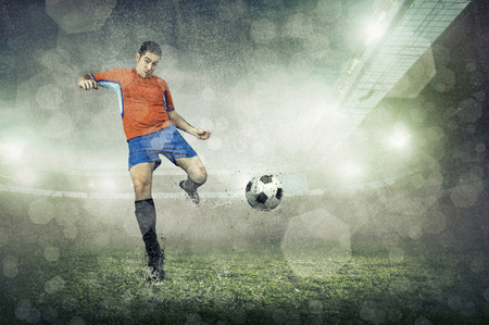 action: Soccer player with ball in action at stadium under rain.