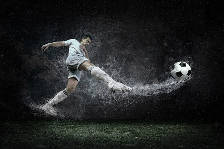 water feature: Splash of drops around football player under water Stock Photo