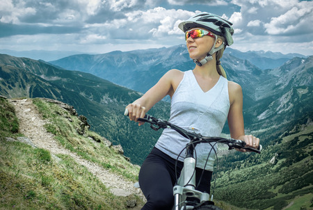 outdoor pursuit: Beautiful woman in helmet and glasses stay on the bicycle around mountains.