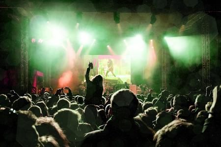 Rockconcert, silhouetten van gelukkige mensen verheffen handen