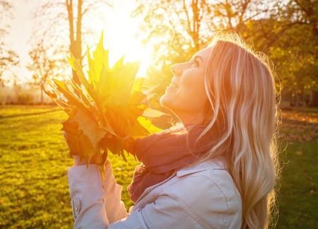 Geluk vrouw met bladeren in de herfst onder zonlicht Stockfoto