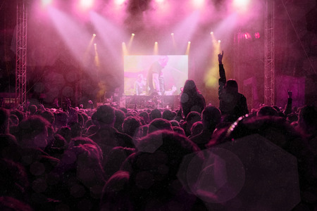 back lighting: Rock concert, silhouettes of happy people raising up hands