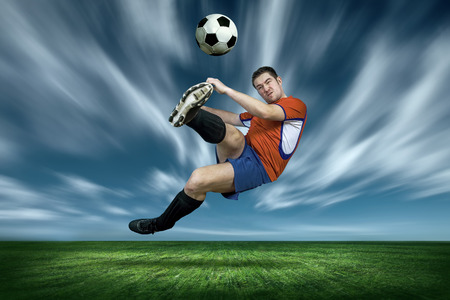 an action: Football player with ball in action under rain outdoors Stock Photo
