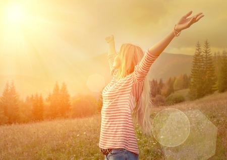 relaxamento: Mulher da felicidade ficar ao ar livre sob a luz solar do por do sol