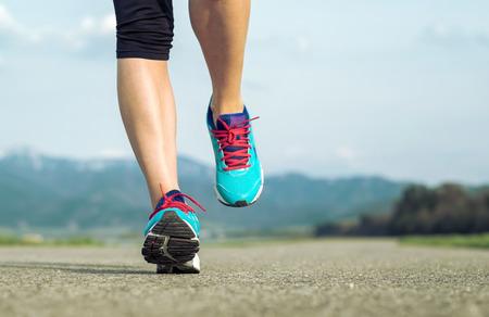 coureur: Runner athl�te pieds fonctionnant sur route sous la lumi�re du soleil.