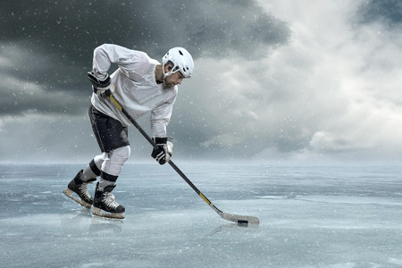 Ice hockey player on the ice in mountains 写真素材