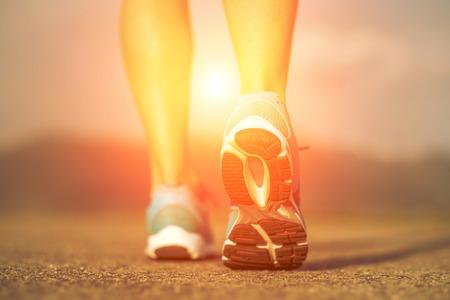 exercise: Runner athlete feet running on road under sunlight. Stock Photo