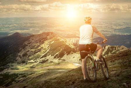 mountain sunset: Men with bicycle aroun mountains beautiful view.