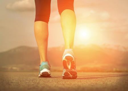feet: Runner athlete feet running on road under sunlight. Stock Photo