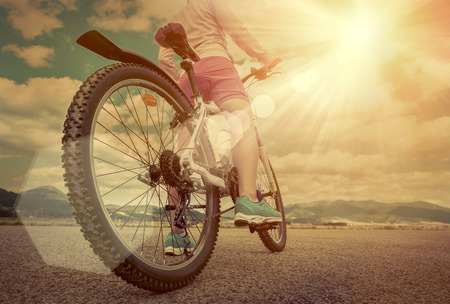 stay beautiful: Beautiful woman in helmet and glasses stay on the bicycle under sky with clouds.