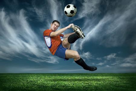 sotto la pioggia: Football player with ball in action under rain outdoors Archivio Fotografico