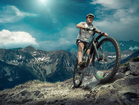 Mann in Helm und Brille zu bleiben auf dem Fahrrad unter Himmel mit Wolken. Standard-Bild