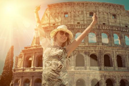 ロマンス: ローマのコロシアムの美しい景色に白い帽子で女性観光客が幸福。