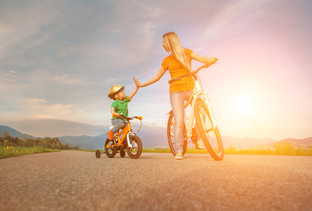 lifestyle caucasian: Happiness Mother and son on the bicycles funning outdoor Stock Photo