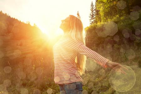 幸せ女性宿泊夕日の日光下での屋外