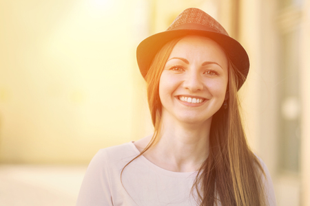 1 woman only: Portrait of young smiling woman in hat on the street