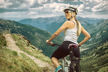 biking: Beautiful woman in helmet and glasses stay on the bicycle around mountains.