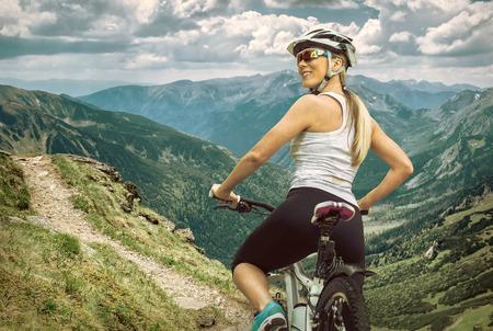 bicicleta: Mujer hermosa en casco y gafas de permanecer en la bicicleta por las montañas.