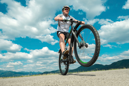헬멧과 안경에 남자 구름과 하늘 아래 자전거에 머물러. 스톡 콘텐츠