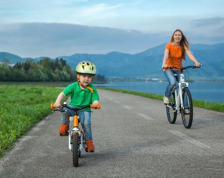 mama e hijo: Madre Felicidad e hijo en las bicicletas Funning aire libre