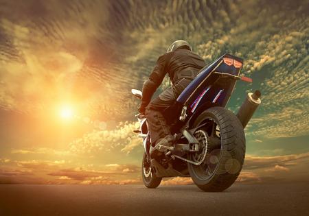 Asiento Hombre en la motocicleta bajo el cielo con nubes Foto de archivo - 44532283