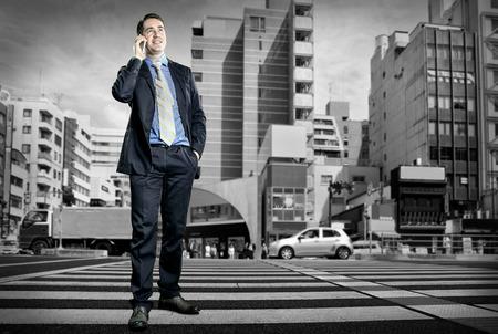 cruce de caminos: Hombre de negocios hablando por teléfono en la encrucijada Foto de archivo