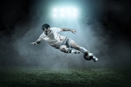 football fan: Soccer player with ball in action outdoors