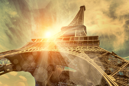 clouds and sky: The Eiffel tower is one of the most recognizable landmarks in the world under sun light