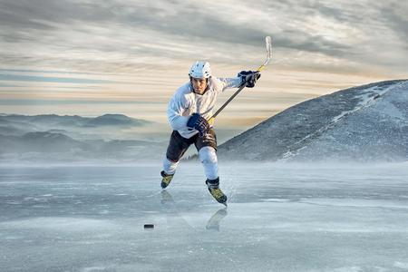 Ijshockeyspeler op het ijs in de bergen