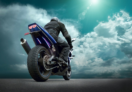 motorcycle racing: Man seat on the motorcycle under sky with clouds Stock Photo