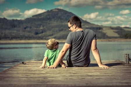 Geluk vader en zoon op de pier op zonnige dag onder de zon.