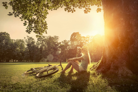 day light: Woman sitting under sun light at day near her bicycle in the park Stock Photo