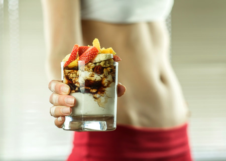 Desert in the hands of fitness female. Standard-Bild